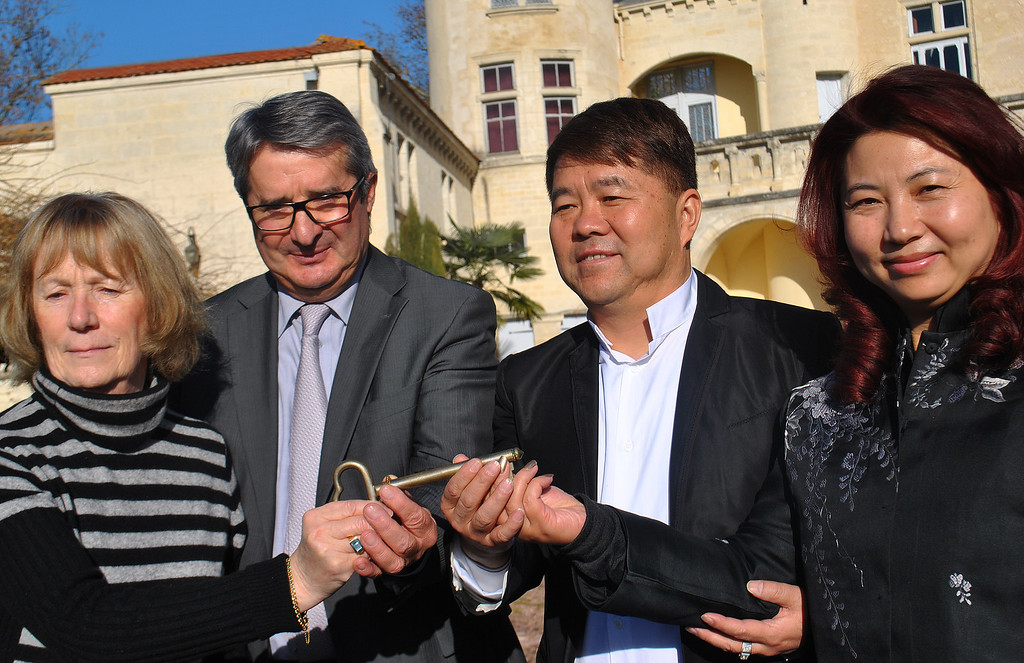 . In this photo taken Friday, Dec. 20, 2013,  Lam Kok, who headed Hong Kong-based company Brilliant Group, second from right, his wife, right, former owner James Gregoire, second from left, and his wife Monique Gregoire, left, pose for photographers after buying the Chateau La Riviere vineyards, near Bordeaux, southwestern France. French authorities say the Chinese magnate, his 12-year-old son and two others, including James Gregoire, died in a helicopter crash on Friday, Dec. 20 as they toured Bordeaux vineyards the businessman had recently purchased. (AP Photo/Marilyn Johnson)
