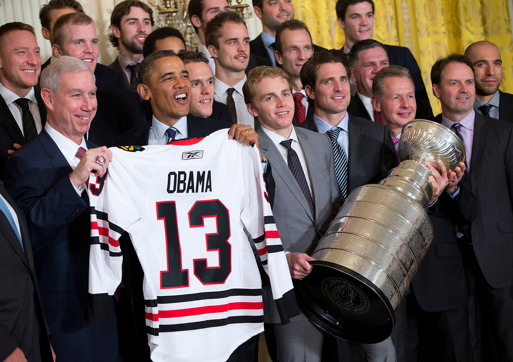 . President Barack Obama holds up a Chicago Blackhawks hockey jersey during a ceremony where he honored the NHL 2013 Stanley Cup champion Chicago Blackhawks hockey team in the East Room of the White House on Monday, Nov. 4, 2013 in Washington. (AP Photo/ Evan Vucci)