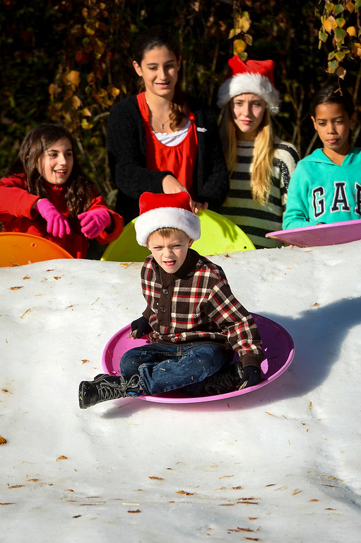 . Vincent Pendley, 6, of Burbank slides down snow on Kling street in Burbank, CA on Monday, December 23, 2013.  Kids along Kling street in Burbank host a fundraiser each year to raise money for the Los Angeles Children\'s Hospital.  The event features snow, cookies, music, hot cocoa and winter fun.   ( Photo by David Crane/Los Angeles Daily News )