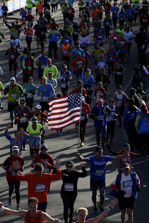 . A man carrying an American flag arrives to the finish line of the 2014 New York City Marathon in New York, Sunday, Nov. 2, 2014. (AP Photo/Seth Wenig)