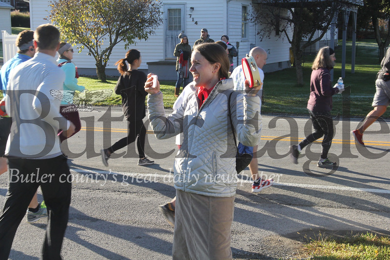 Rachel Smith of Evans City cheers runners along as they begin as half-marathon in Cabot. Photos by Eric Jankiewicz