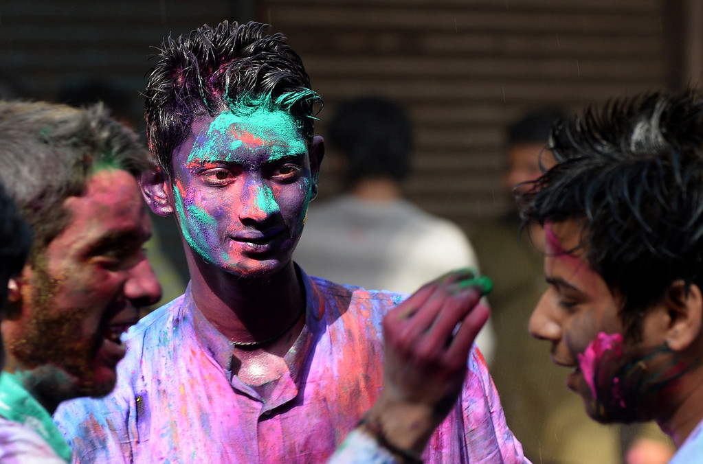 . Indian revelers, cover each other with colored powder,as they celebrate Holi, the Festival of Colors in the old quarters of New Delhi on March 17,2014.  Holi, The Festival of Colors, is a popular Hindu spring festival observed in India at the end of the winter season on the last full moon day of the lunar month.   AFP PHOTO /SAJJAD HUSSAIN/AFP/Getty Images