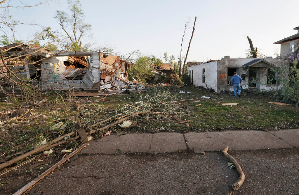 . Bob Hessee checks out property owned by a friend and damaged by a tornado in Baxter Springs, Kan., Monday, April 28, 2014.  A tornado damaged dozens of buildings and injured at least 25 people on Sunday. (AP Photo/Orlin Wagner)