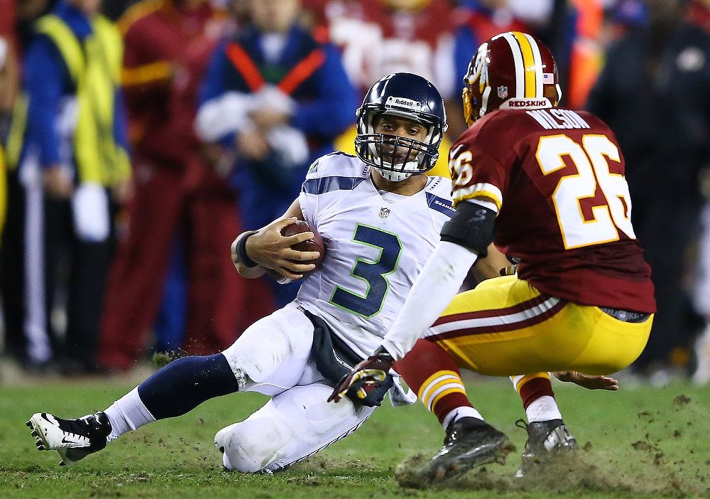 Description of . Russell Wilson #3 of the Seattle Seahawks runs the ball against the defense of Josh Wilson #26 of the Washington Redskins during the NFC Wild Card Playoff Game at FedExField on January 6, 2013 in Landover, Maryland.  (Photo by Al Bello/Getty Images)
