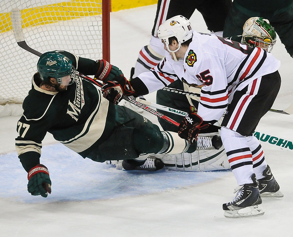 . Minnesota\'s Tom Gilbert, left, falls into Chicago goalie Corey Crawford after being pushed to the ice by Andrew Shaw, right, during the second period.  (Pioneer Press: Ben Garvin)