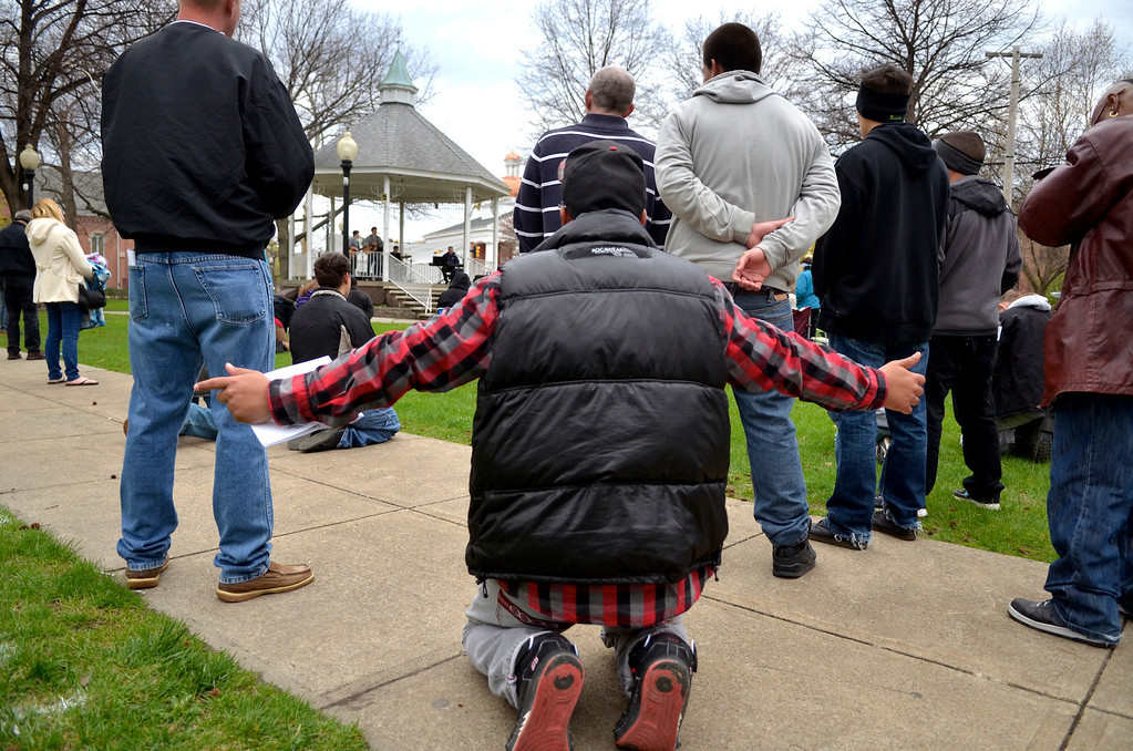 . Jeff Forman/JForman@News-Herald.com Dusten Washington, of PIttsburgh, kneels in prayer  during a National Day of Prayer observance May 1 in Painesville.