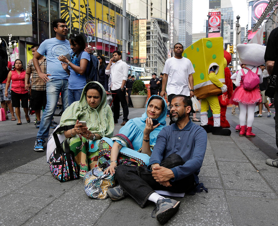 . Members of the Indian-American community gather in Times Square to watch a live stream of Indian Prime Minister Narendra Modi who spoke to a capacity crowd at Madison Square Garden, Sunday, Sept. 28, 2014, in New York. A day after addressing a hushed U.N. General Assembly, where headphone-wearing delegates rarely break into a smile, India\'s new prime minister told a packed and boisterous crowd to help him develop his nation\'s economy, vowing that under his leadership, India won\'t look back. (AP Photo/Julie Jacobson)