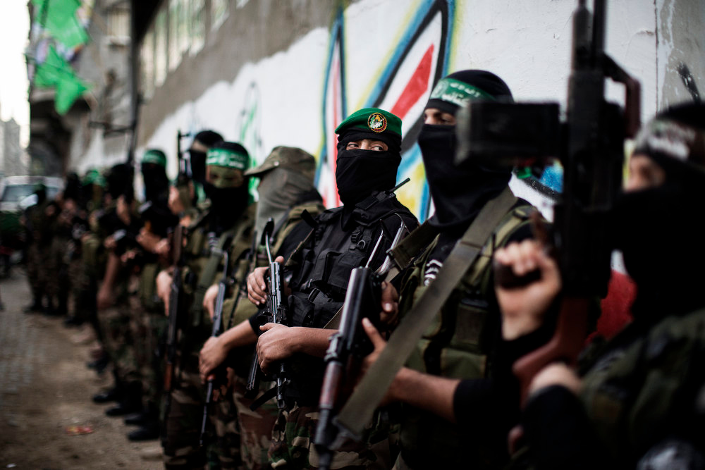 Description of . Gunmen from  the Ezzedine al-Qassam Brigades, the armed wing of Hamas, line up outside the house of their late leader Ahmed Jaabari, after mourners finished visiting his family to pay their condolences in Gaza City on November 22, 2012. Israeli politicians returned to the campaign trail as the streets of Gaza came back to life after a truce ended eight days of bloodshed, with both sides claiming victory while remaining wary. MARCO LONGARI/AFP/Getty Images