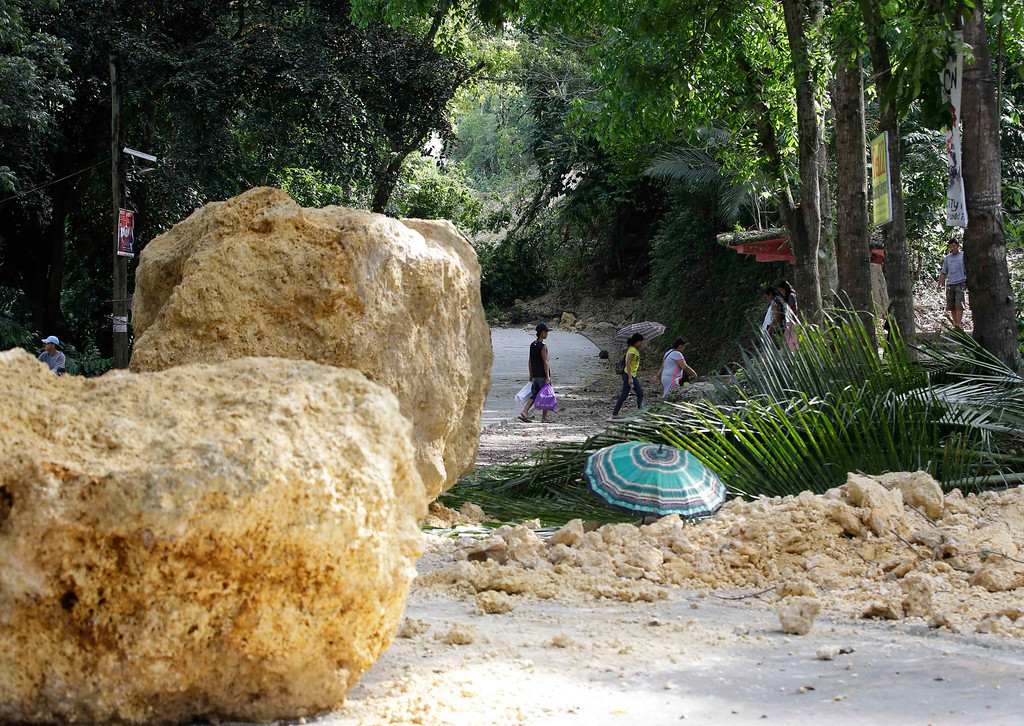 . Huge boulders block the highway in Cortes township, Bohol province in central Philippines Wednesday Oct. 16, 2013, a day after a 7.2-magnitude quake hit Bohol and Cebu provinces.  (AP Photo/Bullit Marquez)