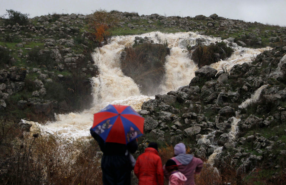 . People watch as water flows in a stream during stormy weather near the Druze village of Majdal Shams on the Golan Heights January 8, 2013. REUTERS/Ammar Awad