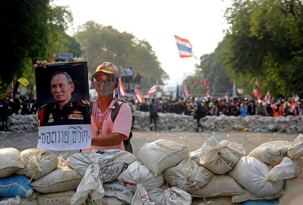 . An anti-government protestor holds a poster of Thai King Bhumibol Adulyadej during a stand-off with Thai Police near Government House in Bangkok on February 18, 2014.   AFP PHOTO / Manjunath Kiran/AFP/Getty Images