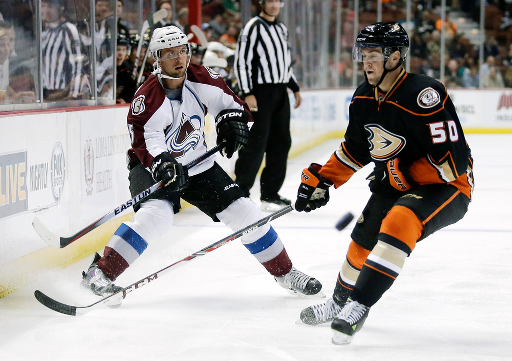 . Colorado Avalanche defenseman Nate Guenin, left, shoots past Anaheim Ducks left wing Nicolas Kerdiles during the first period of an NHL hockey preseason game in Anaheim, Calif., Monday, Sept. 22, 2014. (AP Photo/Chris Carlson)