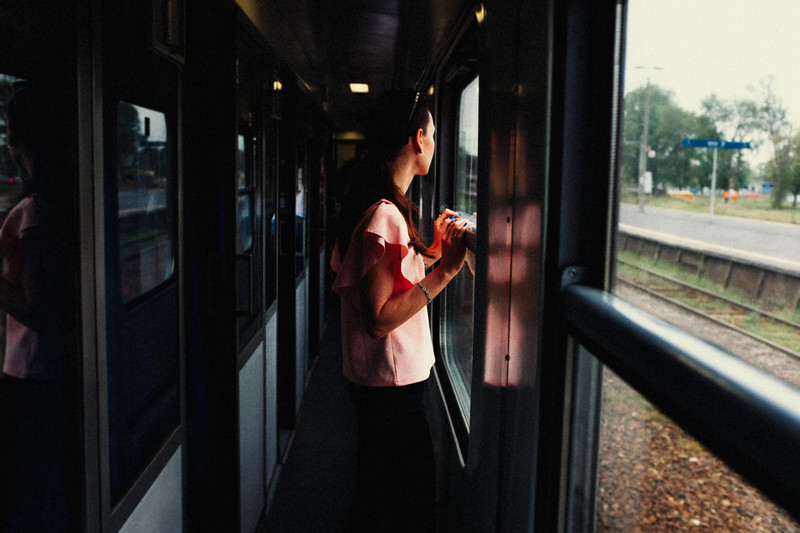 woman on train looking out window street poznan poland erik witsoe summer rain.jpg