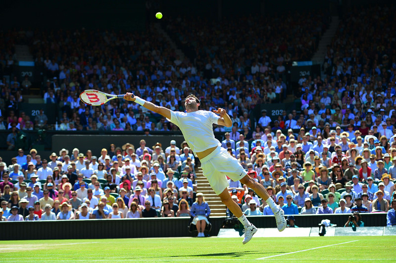 . Bulgaria\'s Grigor Dimitrov jumps to hit a return to Serbia\'s Novak Djokovic during their men\'s singles semi-final match on day 11 of  the 2014 Wimbledon Championships at The All England Tennis Club in Wimbledon, southwest London, on July 4, 2014. (CARL COURT/AFP/Getty Images)
