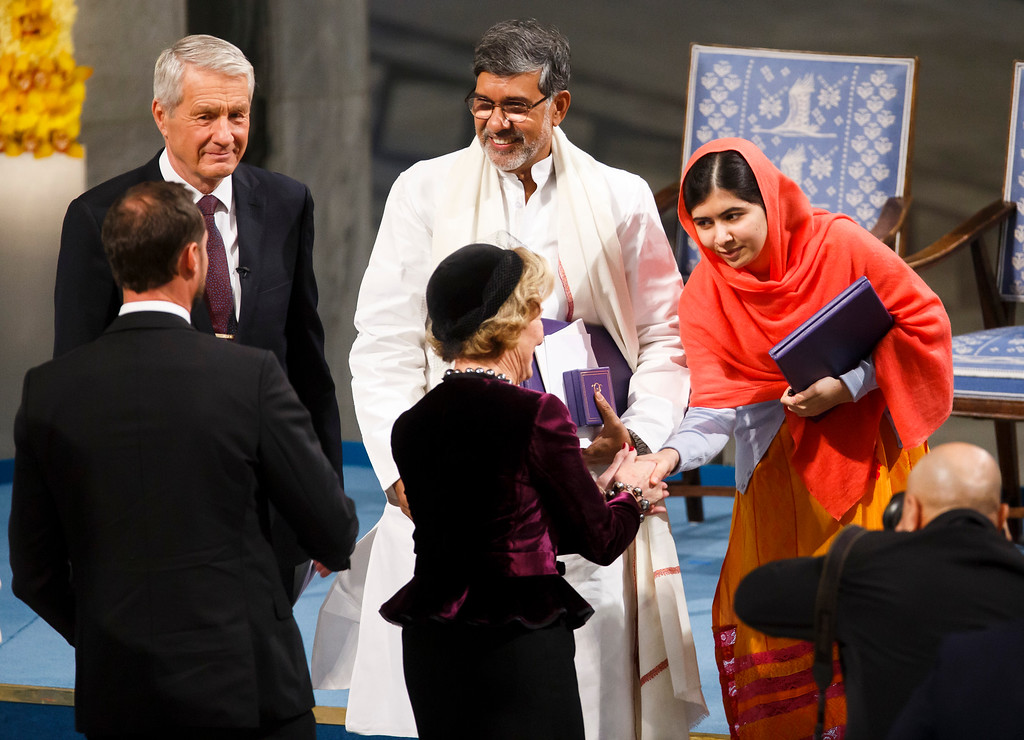 . Nobel Peace prize laureate Malala Yousafzai, right, shakes hands Queen Sonja of Norway, with fellow laureate Kailash Satyarthi, centre, Wednesday Dec. 10, 2014 in Oslo City Hall. Malala Yousafzai and Kailash Satyarthi both received the Nobel Peace Prize on Wednesday, both have campaigned for the rights of children and young people. (AP Photo / Heiko Junge, NTB scanpix) NORWAY OUT