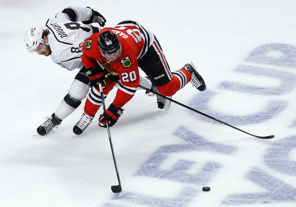 . Chicago Blackhawks left wing Brandon Saad (20) and Los Angeles Kings defenseman Drew Doughty (8) vie for the puck during the first period in Game 5 of the NHL hockey Stanley Cup playoffs Western Conference finals Saturday, June 8, 2013, in Chicago. (AP Photo/Charles Rex Arbogast)