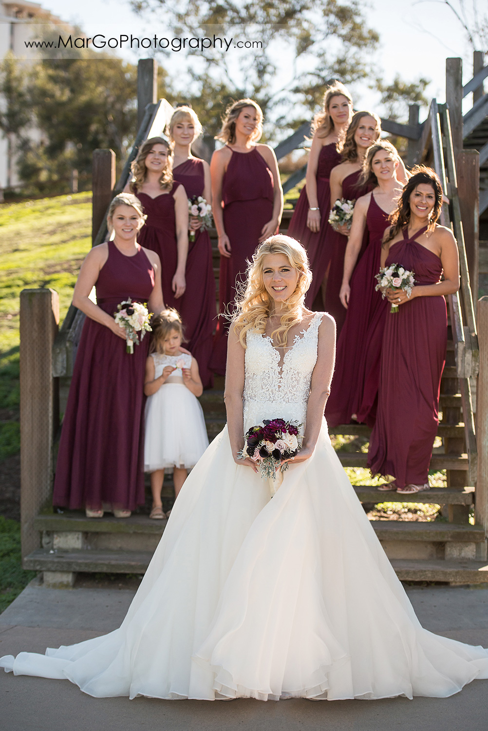 portrait of bride holding bouquet and standing in front of bridesmaids in burgundy dresses at San Diego Mission Bay Park