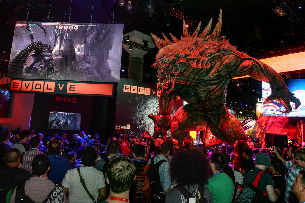 ". People stand next to a monster character from the video game ""Evolve\"" as they watch gamers play the video game at the Electronic Entertainment Expo in Los Angeles on Tuesday, June 10, 2014. (Photo by Watchara Phomicinda)"