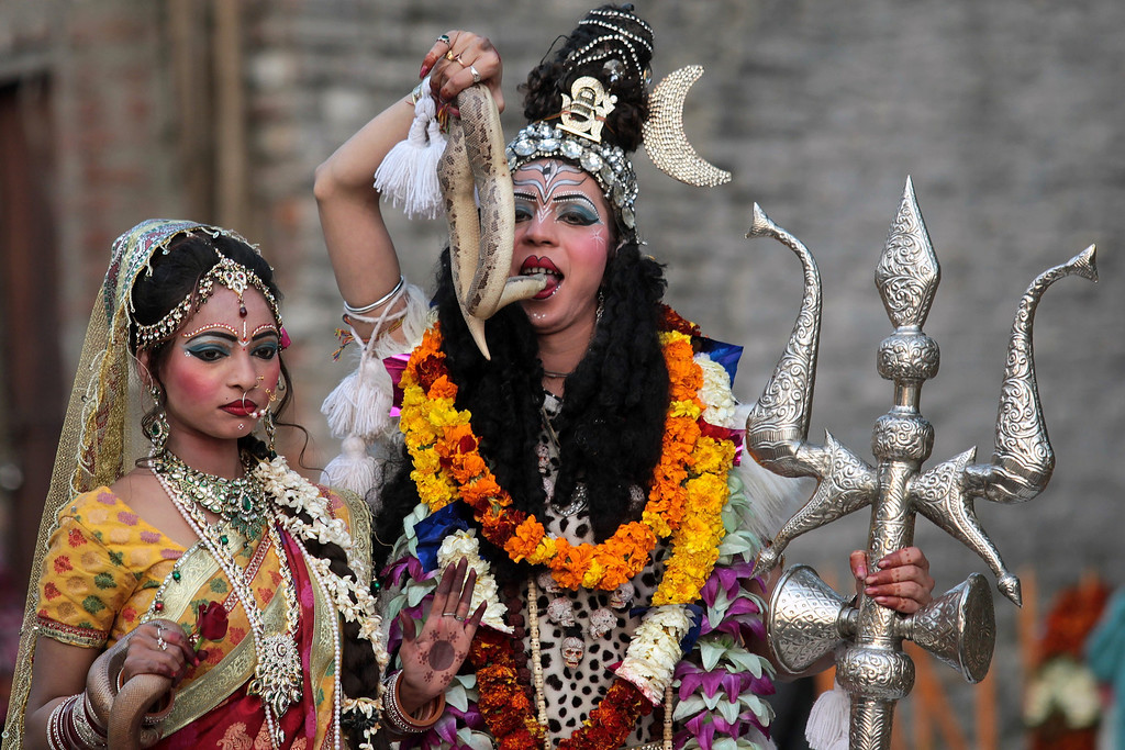 . Indian Hindu devotees dressed as Hindu god Lord Shiva (R), seen holding a snake to her mouth, and Mata Parvati (L) participate in a procession on the eve of the Shivaratri festival in Jammu on February 26, 2014.  AFP PHOTO/STRSTRDEL/AFP/Getty Images
