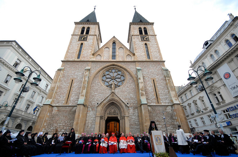 . FILE - In this Sept. 11, 2012 file photo, Orthodox Christian priests and other Christian clergy pray outside the Sarajevo Cathedral in Sarajevo, Bosnia. World War I is just one era in the history of this multicultural city with its legacies of Islamic Ottoman, Jewish, Christian Orthodox and Roman Catholic religions. (AP Photo/Sulejman Omerbasic, File)