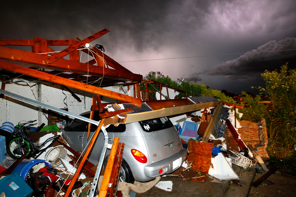 . Lightning strikes from a storm illuminate a home damaged by a tornado on Hyde Park Lane at Country Club Rd. in Cleburne, Wednesday night, May 15, 2013. Cleburne Mayor Scott Cain early Thursday declared a local disaster as schools canceled classes amid the destruction. (AP Photo/The Dallas Morning News, Tom Fox)