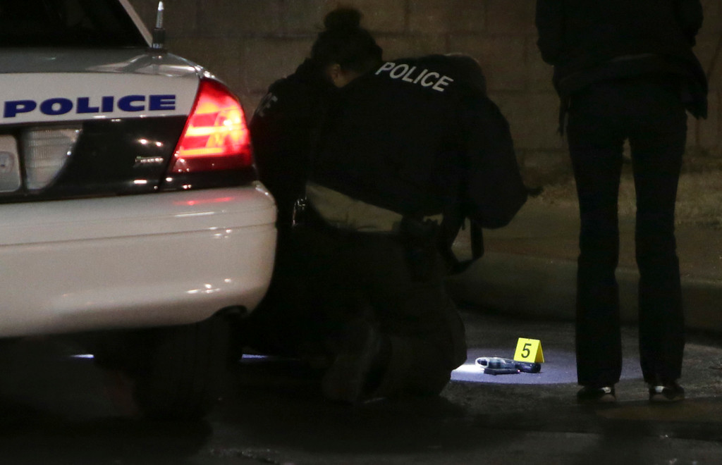 . Police photograph a gun on the ground Wednesday, Dec. 24, 2014, following a shooting Tuesday at a gas station in Berkeley, Mo. St. Louis County police say a man who pulled a gun and pointed it at an officer has been killed. (AP Photo/St. Louis Post-Dispatch, David Carson)