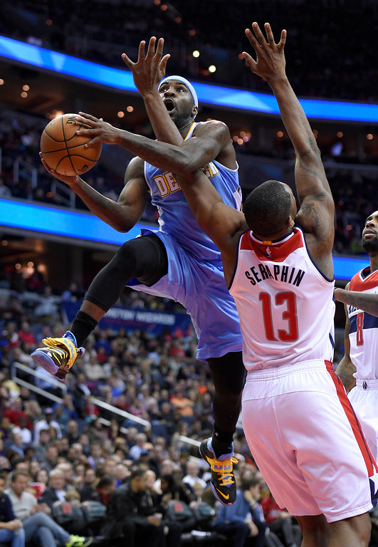 . Denver Nuggets guard Ty Lawson, left, is fouled by Washington Wizards center Kevin Seraphin (13), of France, during the first half of an NBA basketball game, Friday, Dec. 5, 2014, in Washington. (AP Photo/Nick Wass)