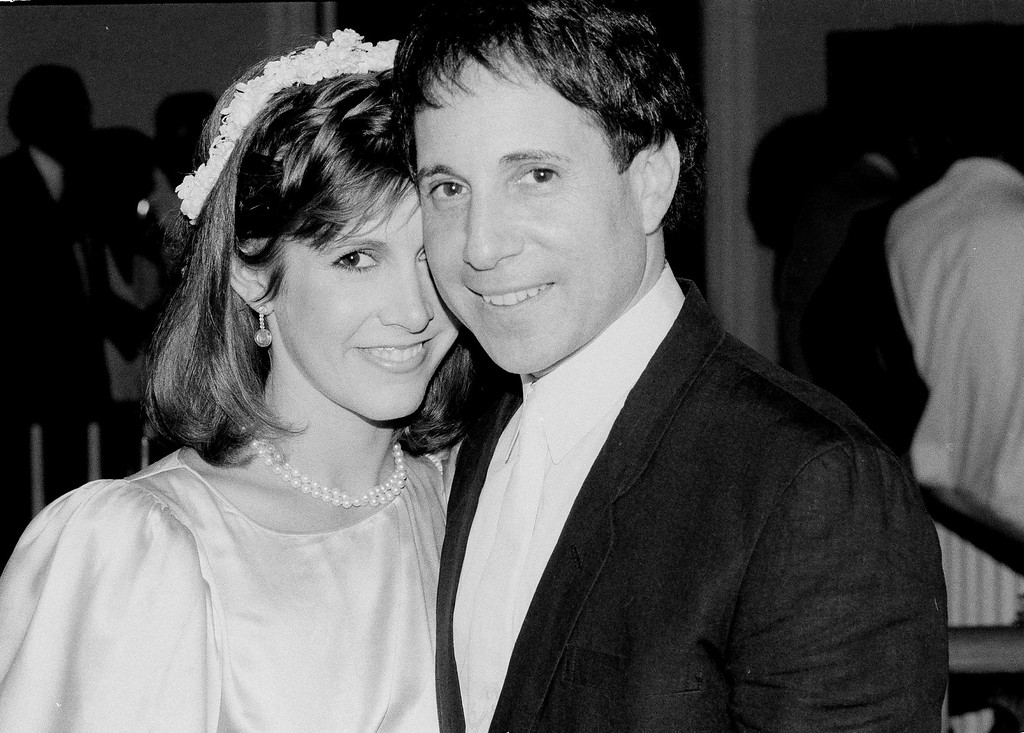 . Singer-composer Paul Simon and actress Carrie Fisher leave the Cathedral of St. John the Devine in New York City, March 11, 1982, after a memorial service for comedian John Belushi. Belushi was found dead in a Los Angeles hotel friday. (AP Photo/Marty Lederhandler)