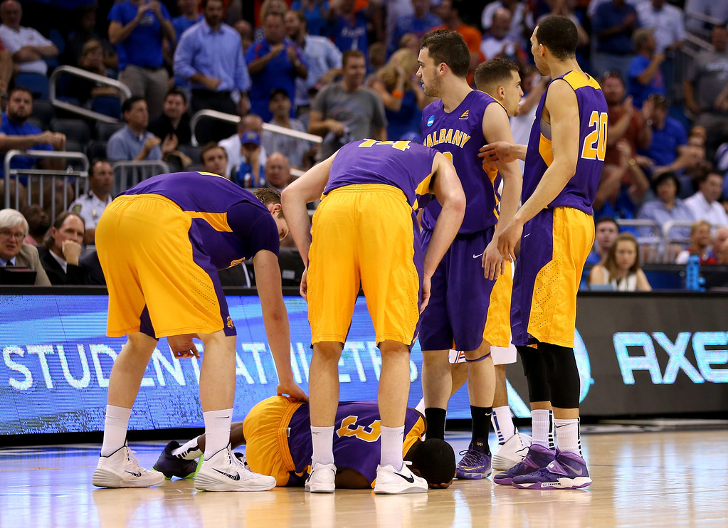 . ORLANDO, FL - MARCH 20:  DJ Evans #3 of the Albany Great Danes reacts in pain after getting kneed unintentionally in the head while taking on the Florida Gators during the second round of the 2014 NCAA Men\'s Basketball Tournament at Amway Center on March 20, 2014 in Orlando, Florida.  (Photo by Mike Ehrmann/Getty Images)