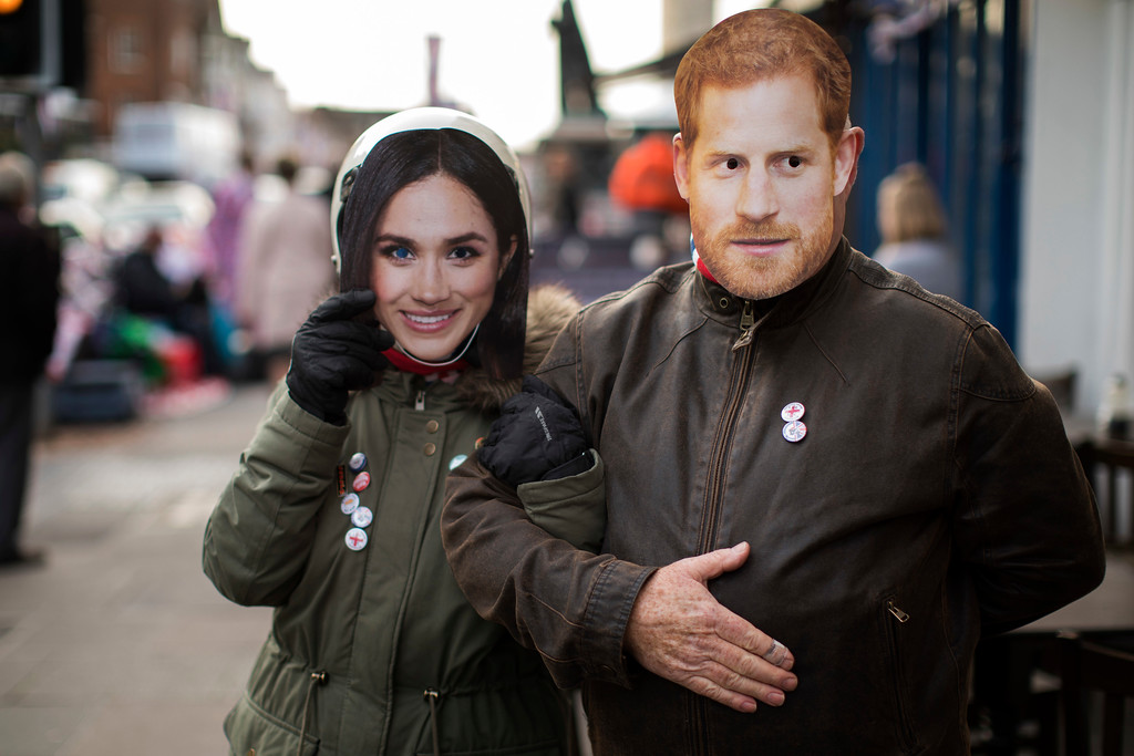 . A couple walk wearing masks with photos of Prince Harry and Meghan Markle in Windsor, England, Wednesday, May 16, 2018. Preparations continue in Windsor ahead of the royal wedding of Britain\'s Prince Harry and Meghan Markle on Saturday May 19. (AP Photo/Emilio Morenatti)