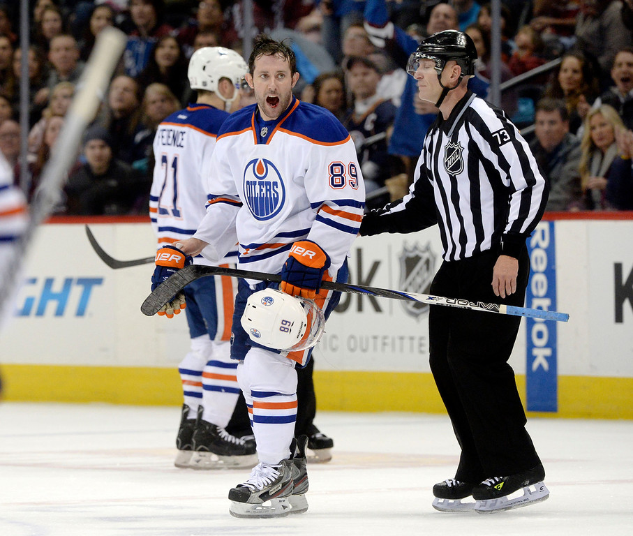 . DENVER, CO. - DECEMBER 19: Edmonton center Sam Gagner (89) was escorted off the ice following a game misconduct penalty for a brutal crosscheck to the face of Paul Stastny in the first period. The Colorado Avalanche hosted the Edmonton Oilers in an NHL game at the Pepsi Center Thursday night, December 19, 2013.  Photo By Karl Gehring/The Denver Post