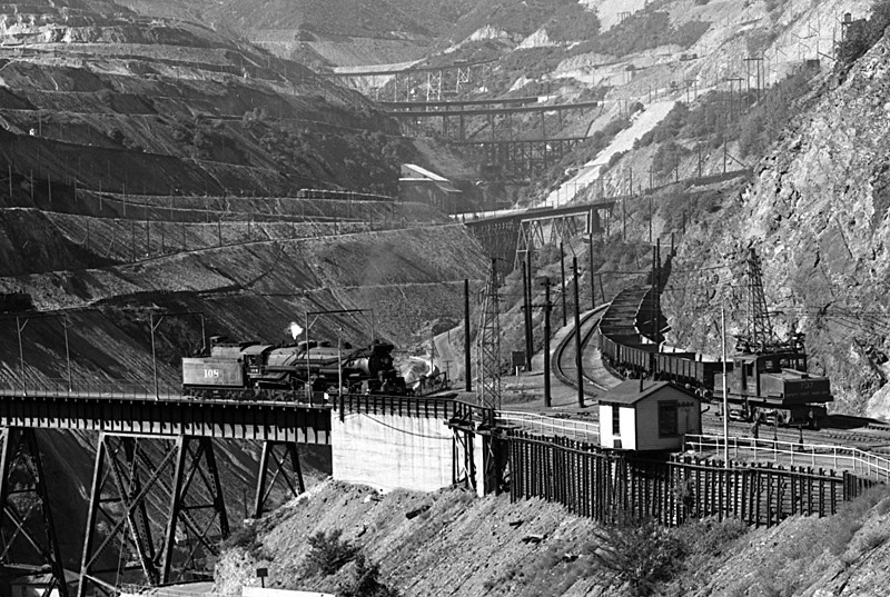 A close examination of this photo reveals that the electric locomotive shown here is one of the four Utah Copper locomotives lettered as Bingham and Garfield, to act as motive power for B&G's common carrier service to other mines in the canyon. This one, number 737, is moving past a cut of GS gondolas to be spotted at one of the other mines, likely the Utah Apex mine further up Carr Fork.