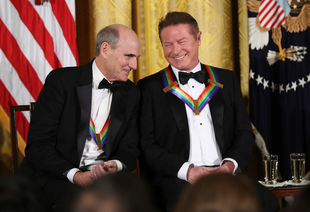 . Recipient of the 2016 Kennedy Center Honors musician James Taylor, left, speaks to Don Henley, a member of the rock band the Eagles, as he is recognized during a reception in their honor in the East Room of the White House in Washington, Sunday, Dec. 4, 2016, hosted by President Barack Obama and first lady Michelle Obama. (AP Photo/Manuel Balce Ceneta)
