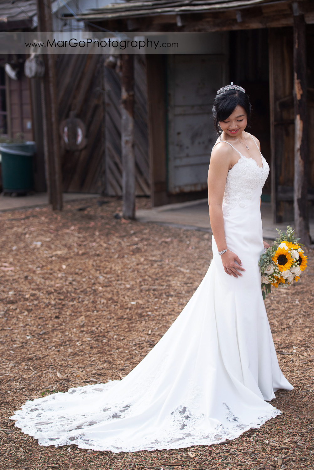 full body portrait of the bride in white dress with yellow flower bouquet at Long Branch Saloon & Farms in Half Moon Bay