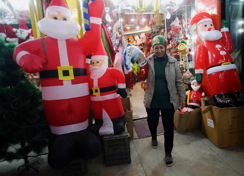 . An Iraqi Christian leaves a store after she bought Christmas decoration items in central Baghdad, Iraq, Wednesday, Dec. 24, 2014. Although the number of Christians has dropped in Iraq, Christmas, a national holiday in Iraq, is very popular in the capital. (AP Photo/Karim Kadim)