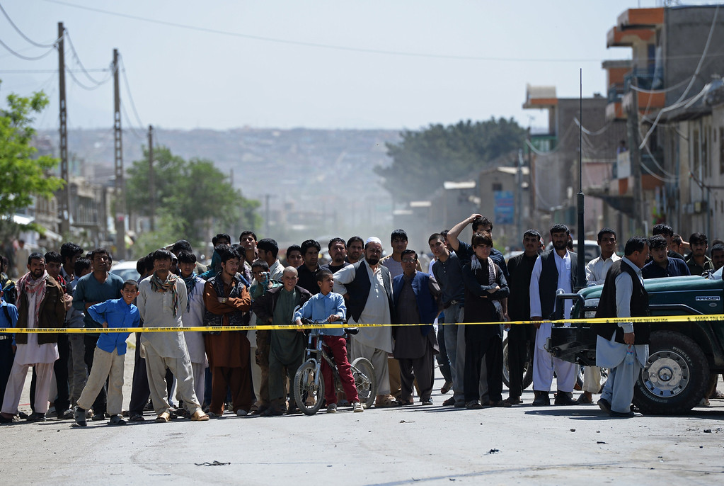 . Afghan men and children look on at the site of a suicide attack in Kabul on May 16, 2013.  AFP PHOTO/ Massoud HOSSAINI/AFP/Getty Images