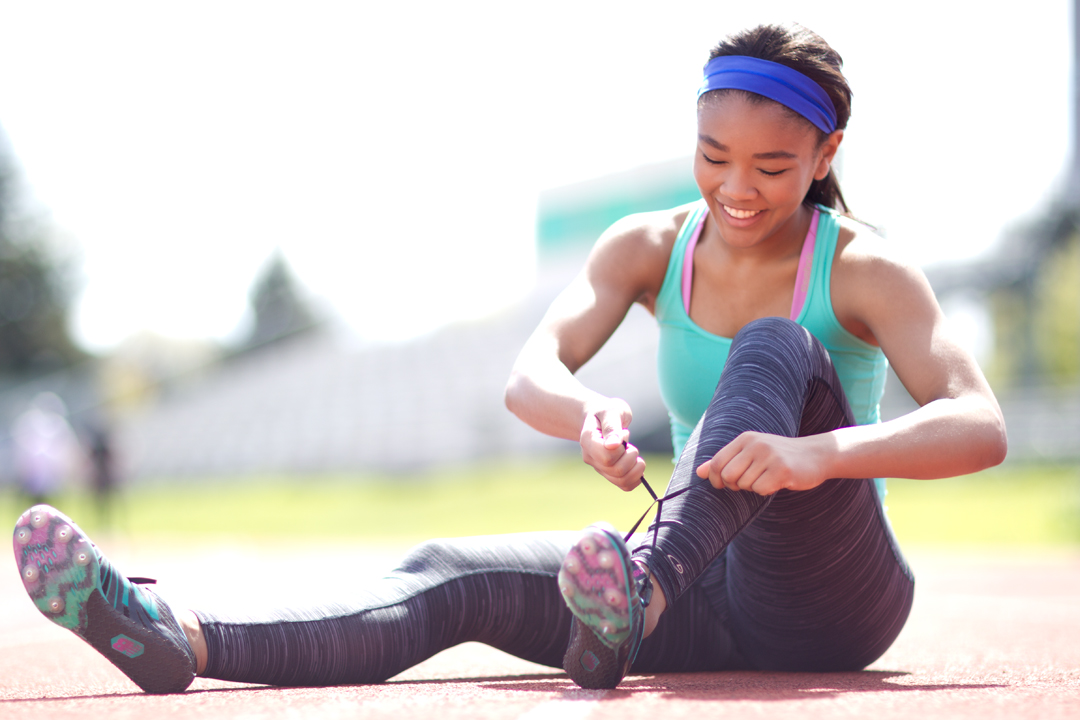 fitness girl lacing up track spikes on track