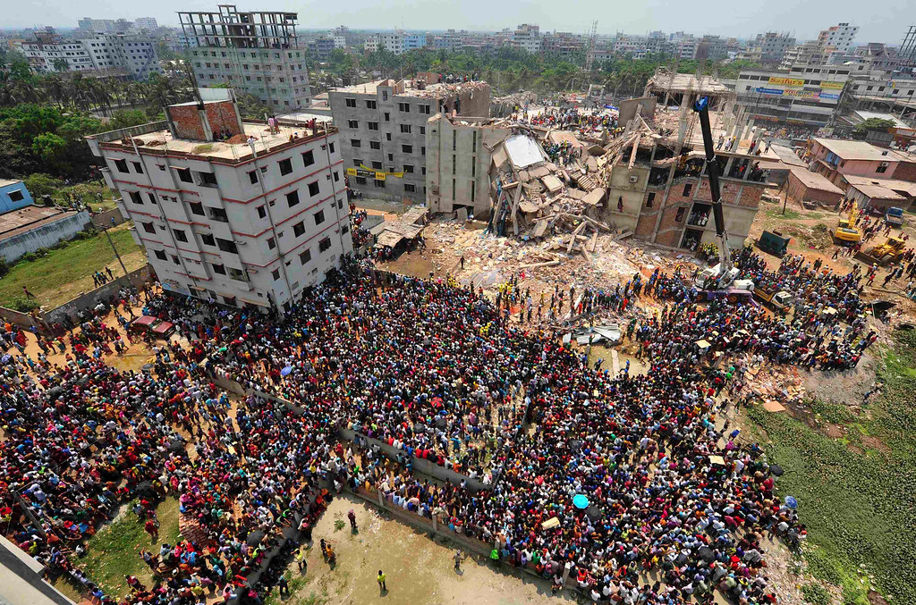 . People gather in front of Rana Plaza building as rescue workers continue their operations, in Savar, 30 km (19 miles) outside Dhaka April 25, 2013. Survivors from the garment factory that collapsed in Bangladesh killing at least 228 people described on Thursday a deafening bang and tremors before the eight-floor building crashed down under them. REUTERS/Stringer