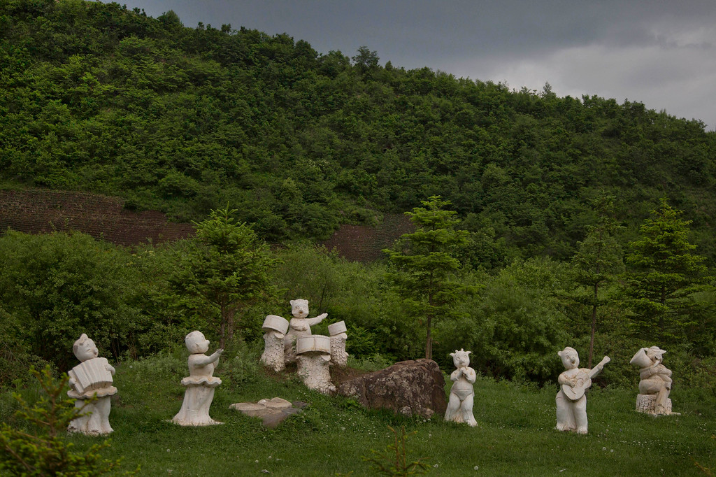""". In this June 16, 2014 photo, statues of animals playing musical instruments stand along the roadside south of Samsu, North Korea in Ryanggang province. The Associated Press was granted permission to embark on a weeklong road trip across North Korea to the countryís spiritual summit Mount Paektu. The trip was on North Korea\'s terms.  An AP reporter and photographer couldn\'t interview ordinary people or wander off course, and government \""""minders\"""" accompanied them the entire way. (AP Photo/David Guttenfelder)"""