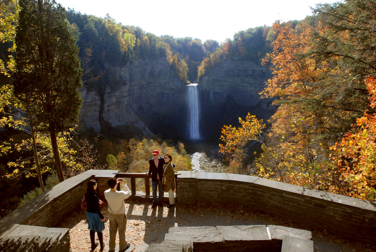 People posing on an overlook in front of a waterfall.