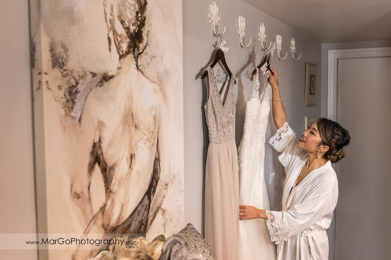 bride reaching her wedding dress at Sunol's Casa Bella bridal suite