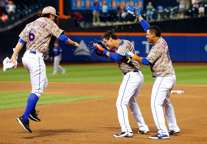. Wilmer Flores #4 of the New York Mets celebrates his ninth inning game winning sacrifice fly against the Colorado Rockies with teammates Juan Lagares #12 and Matt den Dekker #6 at Citi Field on September 8, 2014 in the Flushing neighborhood of the Queens borough of New York City.  (Photo by Jim McIsaac/Getty Images)