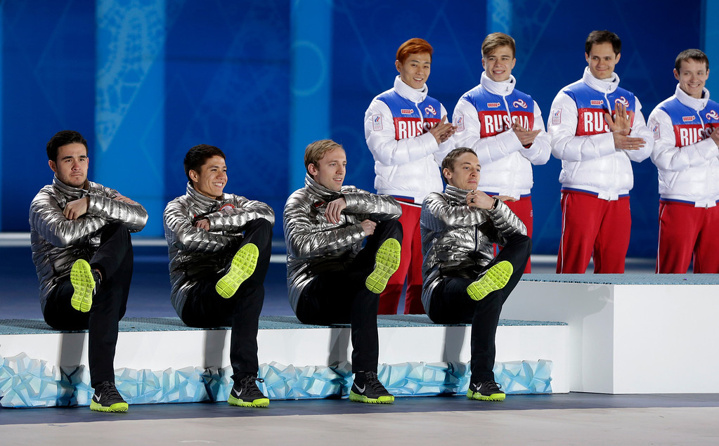 . The team from the United States, who won the silver medal in the men\'s short track speedskating 5,000-meter relay, pose while sitting on the podium as gold medalists from Russia, right, applaud during their medals ceremony at the 2014 Winter Olympics, Saturday, Feb. 22, 2014, in Sochi, Russia. (AP Photo/Darron Cummings)