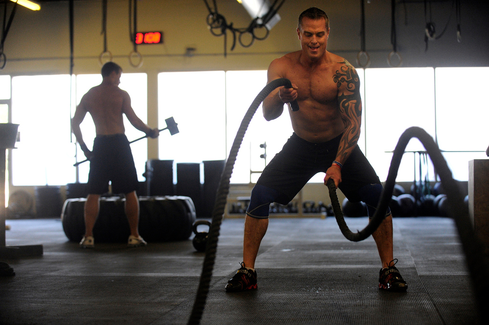 . Dave Gordon works out on the battle ropes during the workout of the day at Crossfit South in Aurora, Colorado on June 27, 2014. Crossfit South offers classes every day of the week. (Photo by Seth McConnell/The Denver Post)