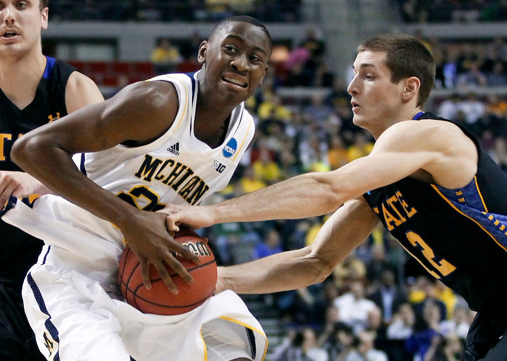 . South Dakota State guard Brayden Carlson, right, tries to steal the ball from Michigan guard Caris LeVert diuring the first half of a second-round game of the NCAA men\'s college basketball tournament Thursday, March 21, 2013, in Auburn Hills, Mich. (AP Photo/Duane Burleson)