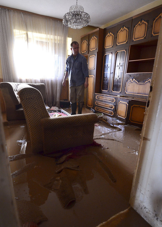 . A man stands in the living room of his flooded house in Sveti Nikole, central Macedonia, Tuesday, Feb. 26, 2013. Three days of heavy rain have flooded hundreds of homes in eastern and central Macedonia, destroyed at least two bridges and cut off dozens of villages, causing power cuts and shortages of drinking water. (AP Photo/Boris Grdanoski)