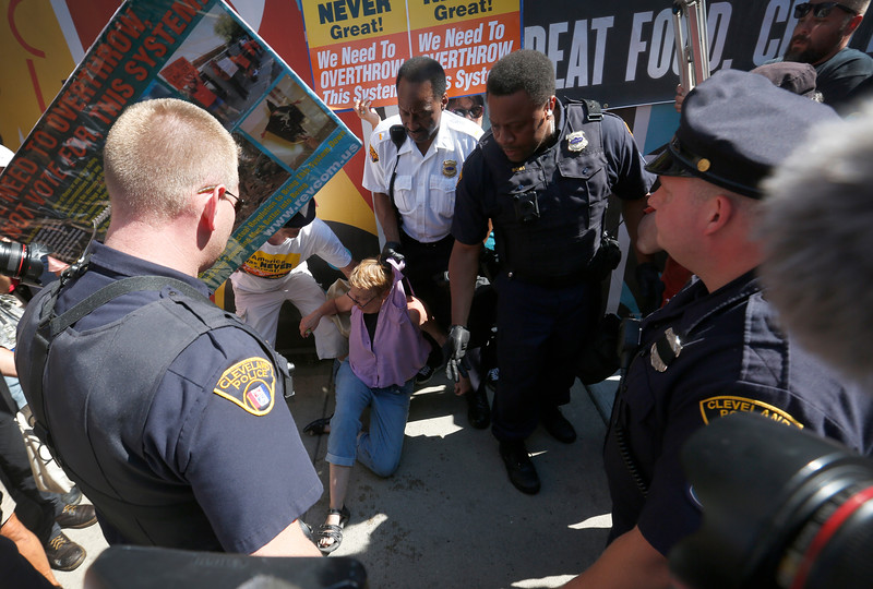 Cleveland police officers arrest a protestor after she attempted to burn a flag near the Republican National Convention in downtown Cleveland, Ohio on July 20, 2016.