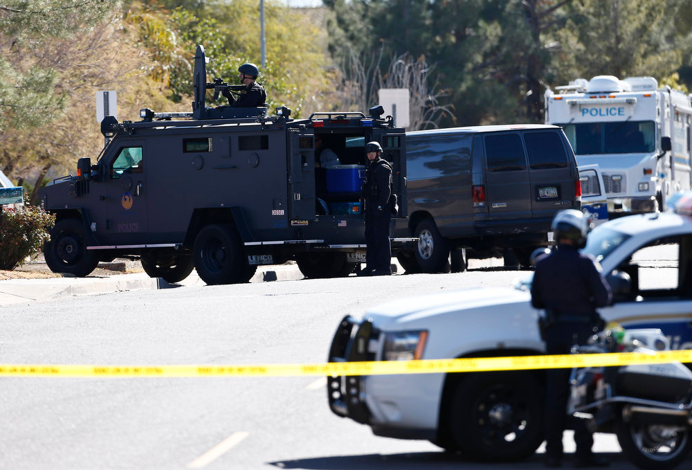 Description of . Members of the Phoenix Police Department, including the SWAT team, back left, surround the home of a suspected gunman who opened fire at a Phoenix office building, wounding three people, one of them critically, and setting off a manhunt that led police to surround his house for several hours before they discovered he wasn't there, Wednesday, Jan. 30, 2013, in Phoenix. Authorities believe there was only one shooter, but have not identified him or a possible motive for the shooting. They don't believe the midmorning shooting at the complex was a random act. (AP Photo/Ross D. Franklin)