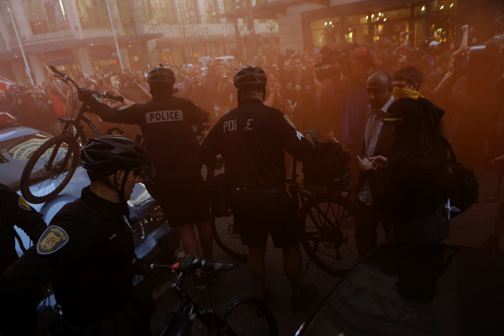 . Police create a barrier with their bicycles as protesters deploy smoke and march during a May Day march that began as an anti-capitalism protest and turned into demonstrators clashing with police Wednesday, May 1, 2013, in downtown Seattle. (AP Photo/The Seattle Times, Bettina Hansen)
