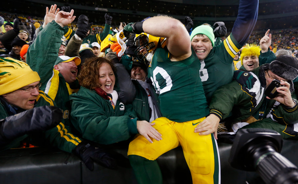 Description of . Green Bay Packers fullback John Kuhn celebrates with fans after scoring a touchdown during the first half of an NFL wild card playoff football game against the Minnesota Vikings Saturday, Jan. 5, 2013, in Green Bay, Wis. (AP Photo/Mike Roemer)